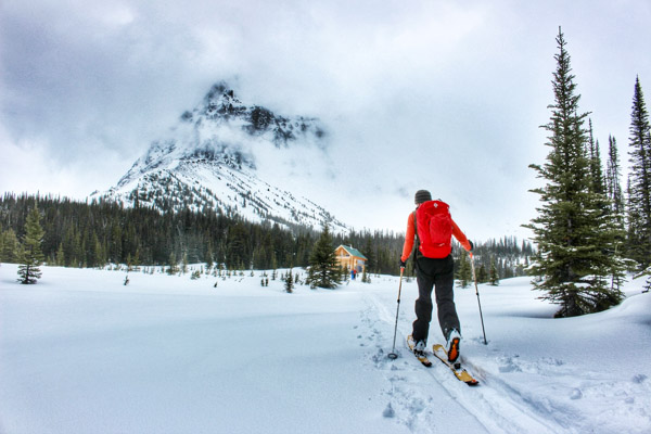 Man ski touring through a meadow towards the Mallard Mountain Lodge