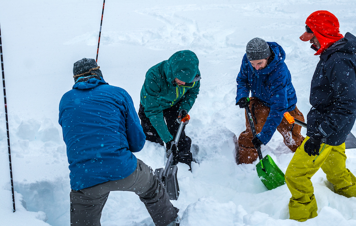 Group practicing digging out a buried person with their avalanche shovels