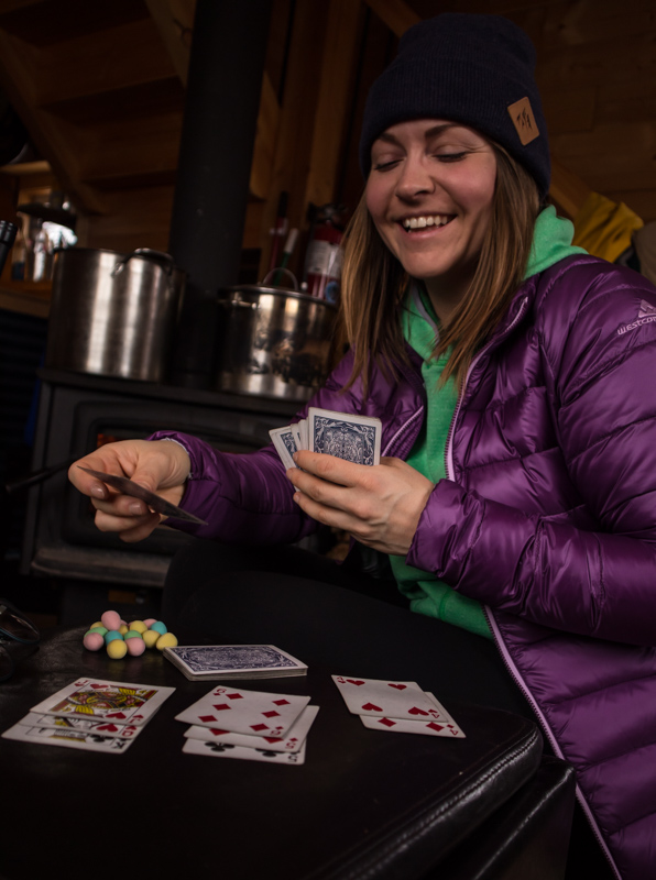 Woman playing cards in front of the fire at the Mallard Mountain Lodge