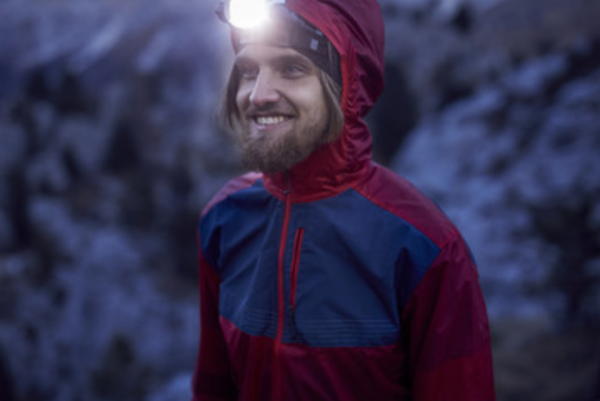 Man smiling at dusk wearing a headlamp