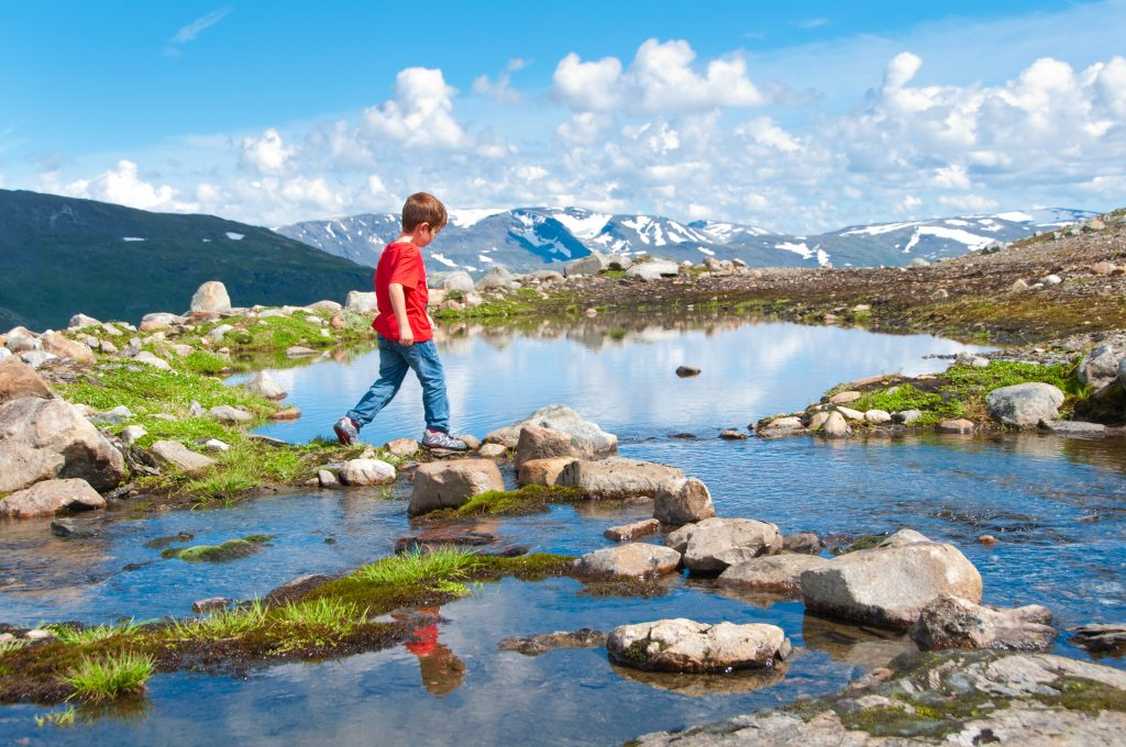 Child crossing mountain lake