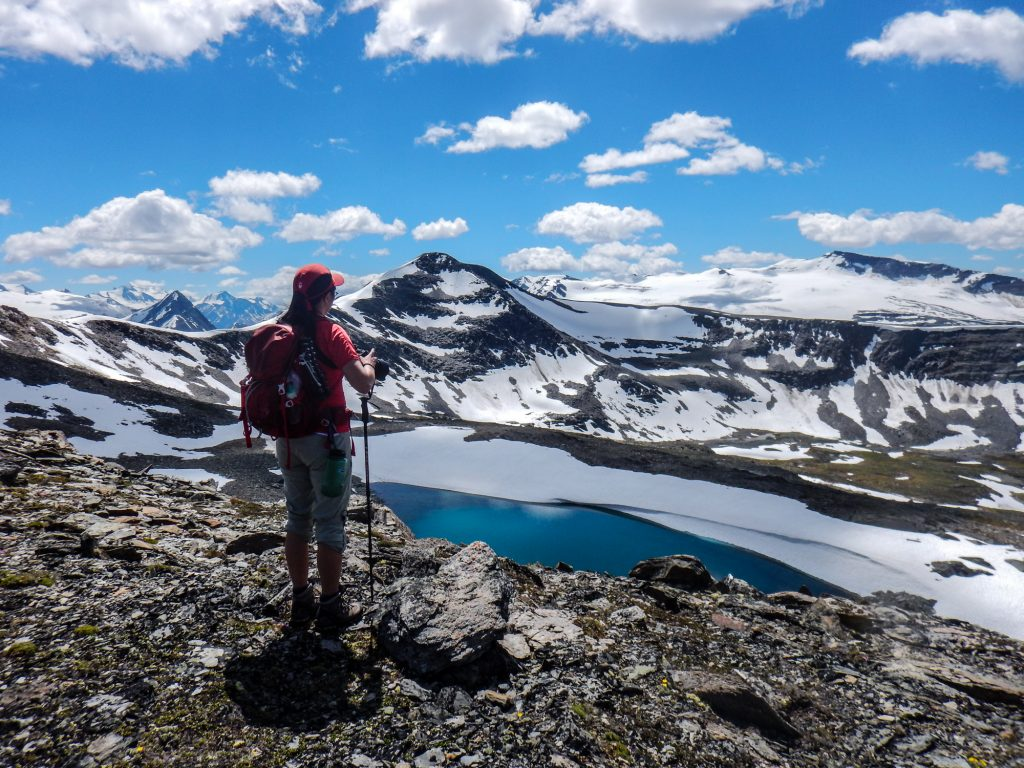 Hiker stood at the edge of a glacier lake in the Rocky Mountains