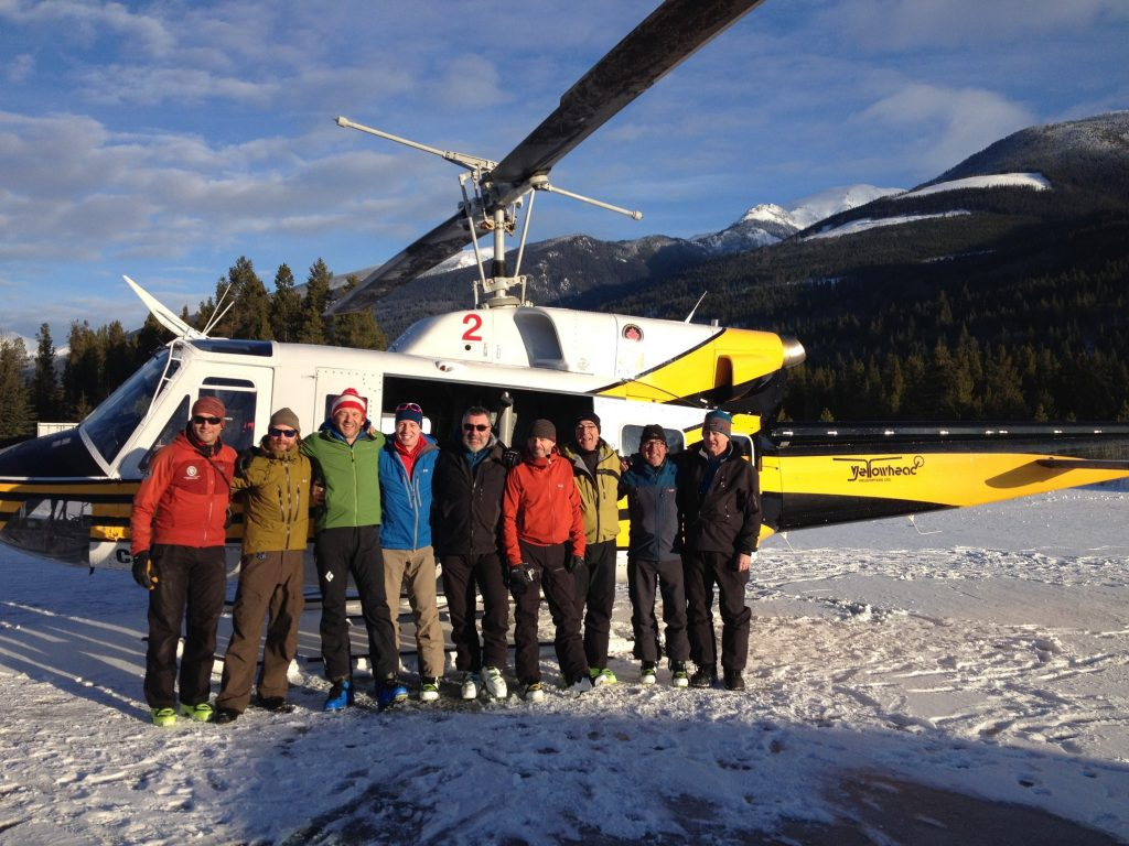 Group of men posing for photo in front of helicopter on snow