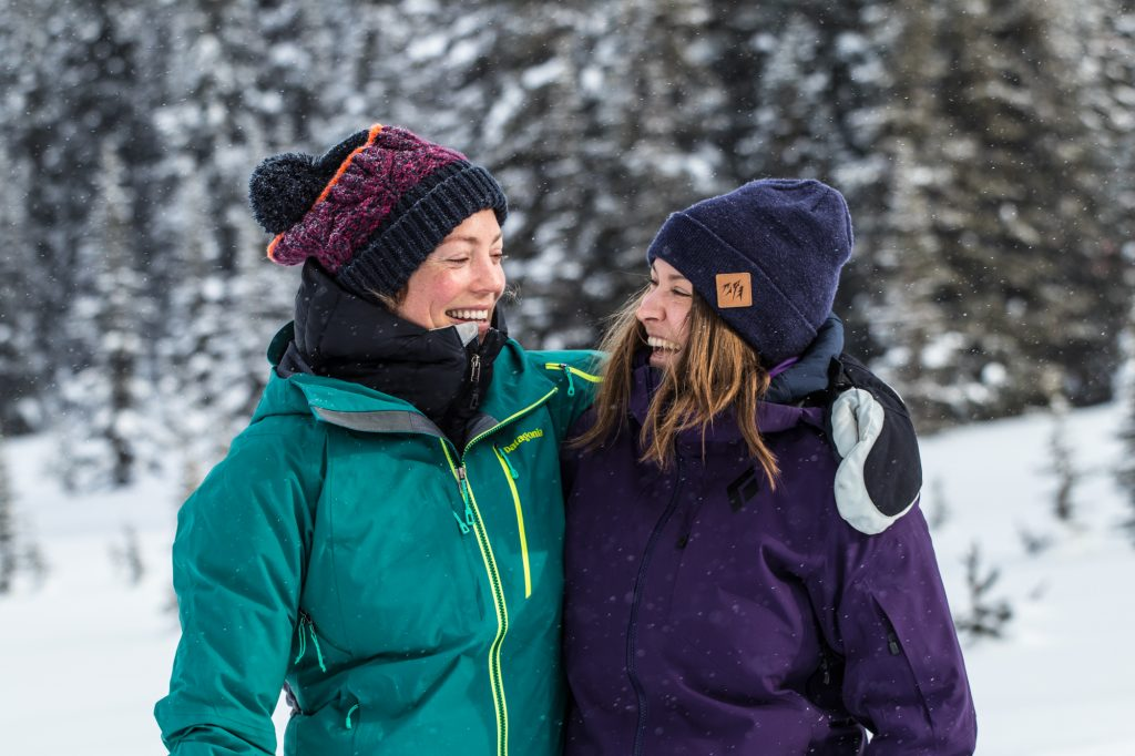 Two women in ski gear with arms over each others shoulder laughing while standing out in the snow