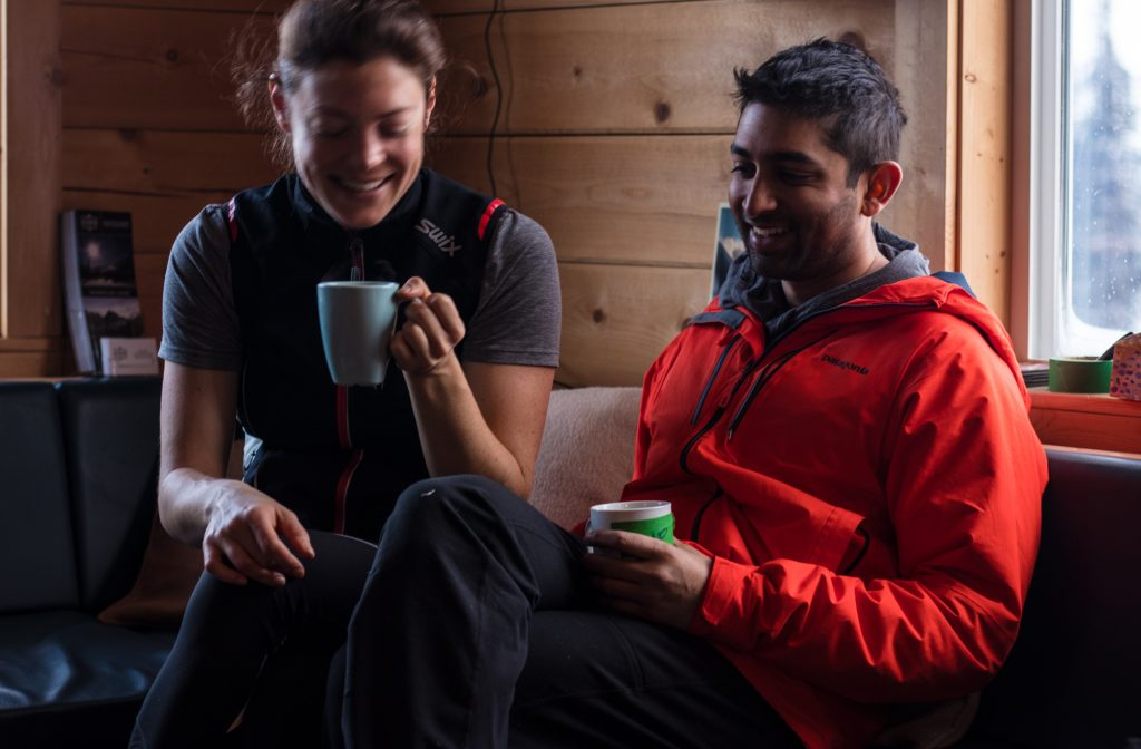 Couple smiling and enjoying coffee at a backcountry ski lodge in BC