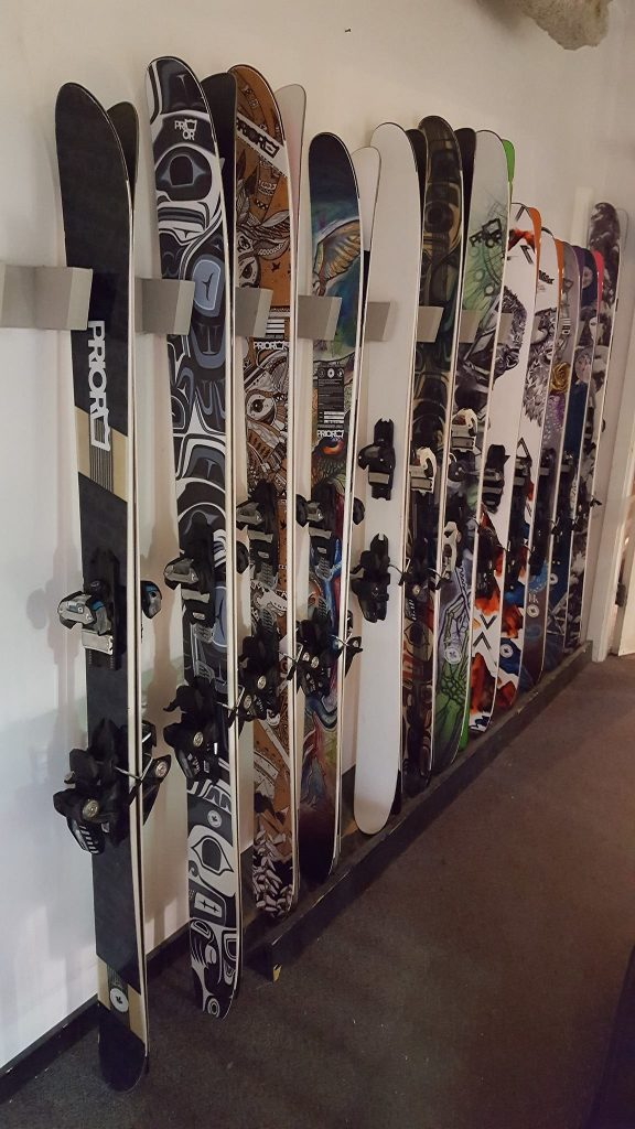 Skis and snowboards in a rack at Prior in Whistler