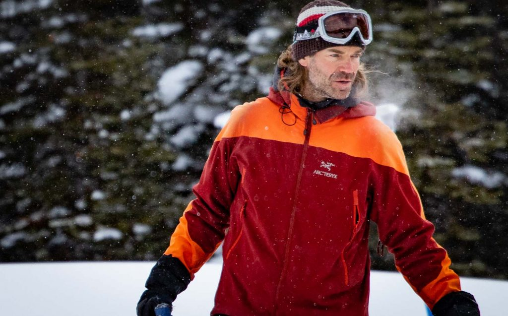 Upper body shot of man standing in ski touring clothing layers