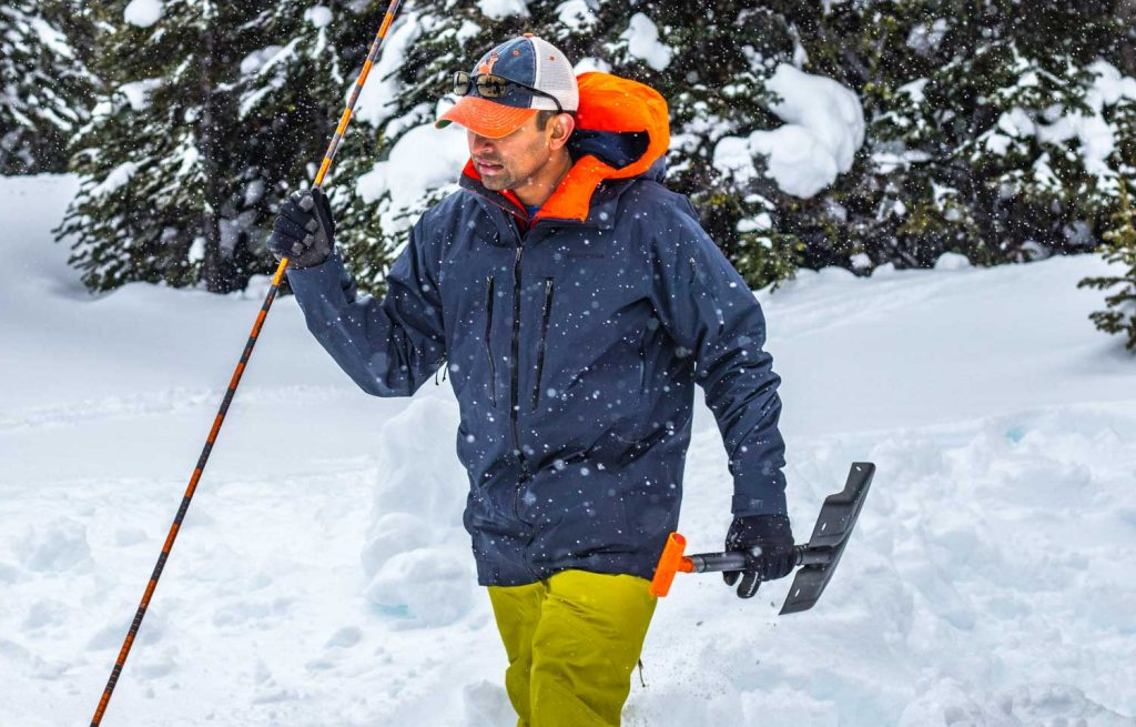 Man carrying avalanche shovel and probe