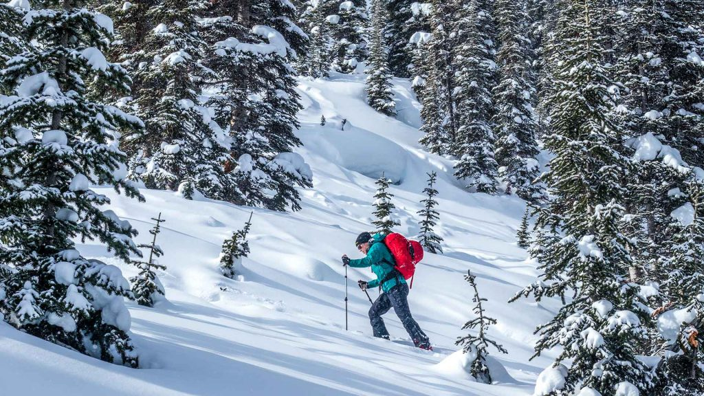 person ski touring uphill at mallard mountain lodge