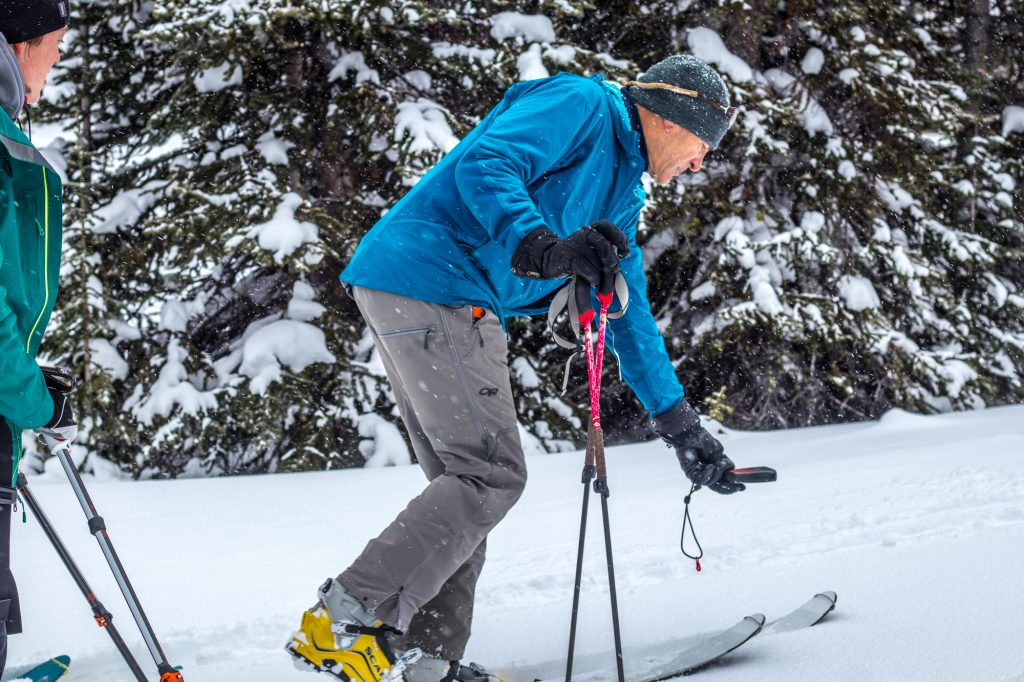 Ski guide testing transceiver in the backcountry